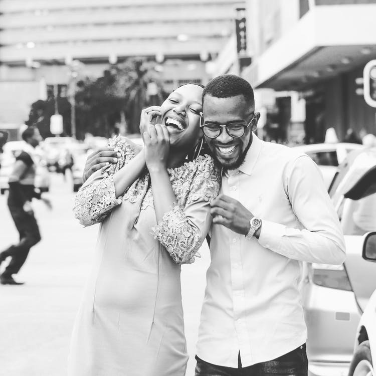 Grayscale Photography of Man and Woman Standing and Laughing