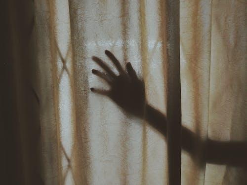 Human Hand Behind Brown Curtain