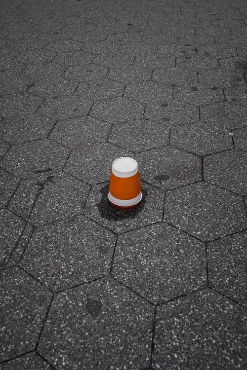 Brown and White Plastic Cup Upside Down on Gray Pavement