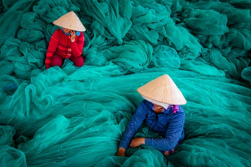 Two Women Surrounded with Green Fish Nets