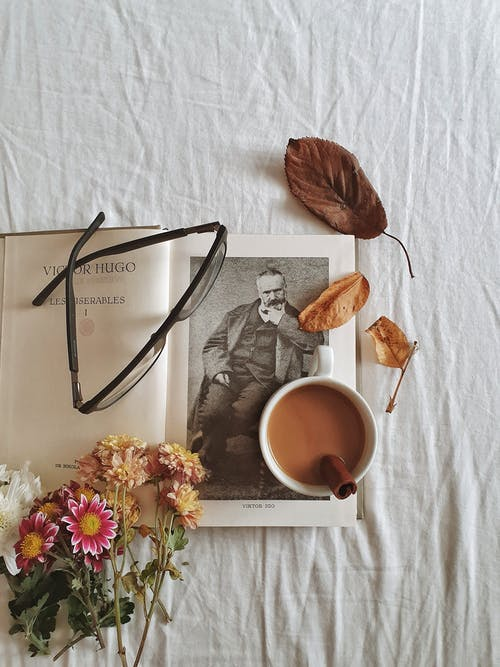 Flowers, Book, Eyeglasses and Cup of Coffee with Cinnamon Stick