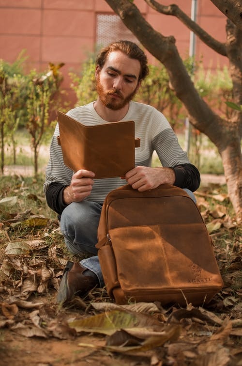 Selective Focus Photography of Man Reading Book Beside Tree