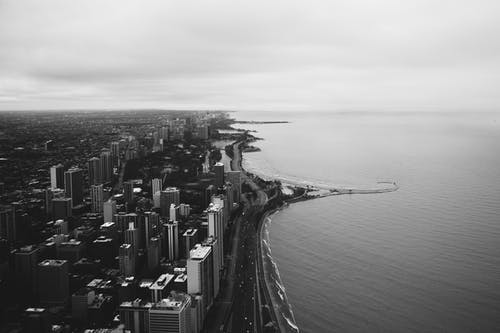 Grayscale Photography of City Buildings Near Body of Water