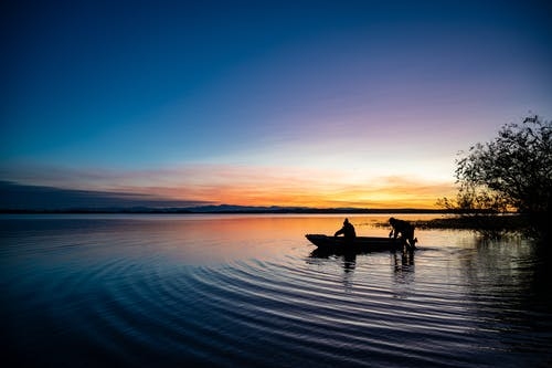 Silhouette of Person Riding Boat on Body of Water