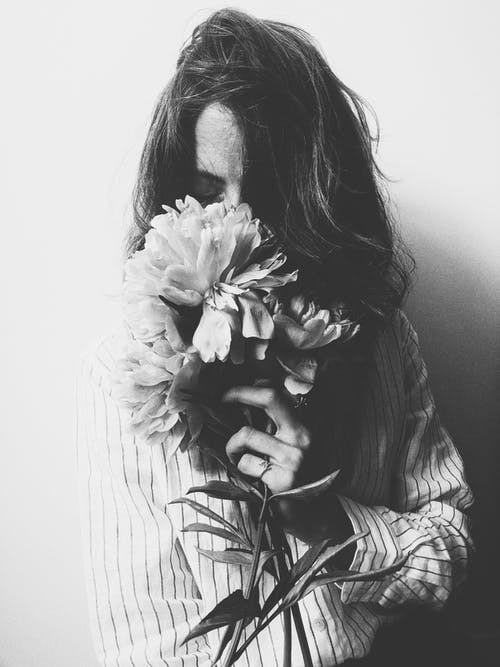 Grayscale Photography of Woman Holding Flowers