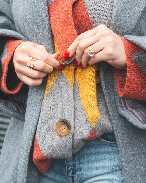 Woman Wearing Multicolored Sweater and Holding Its Buttons