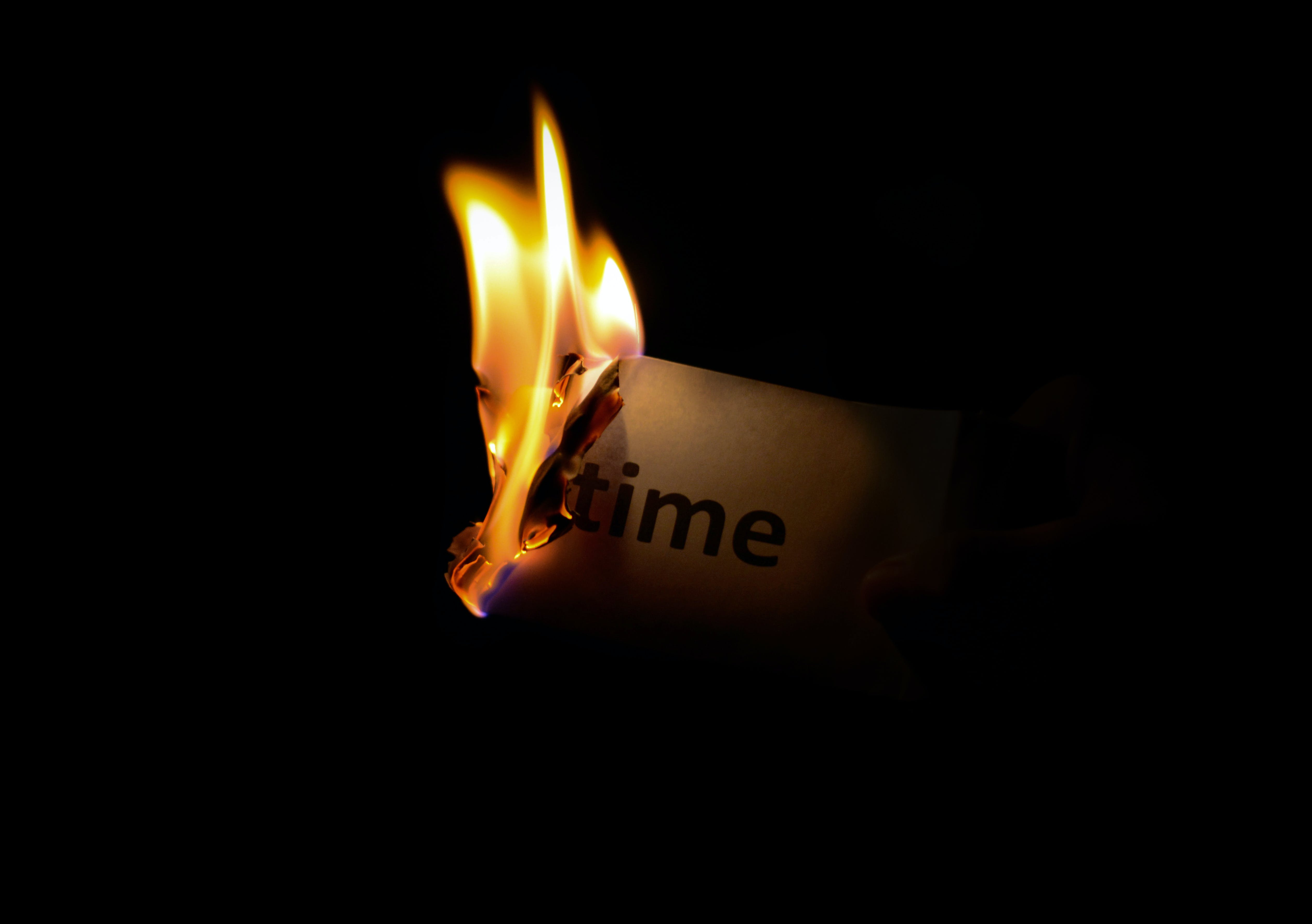 Person Holding Burning Paper in Dark Room