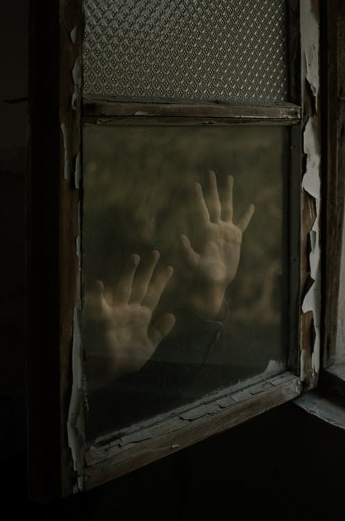 Unknown Person Putting Hands on Glass Window