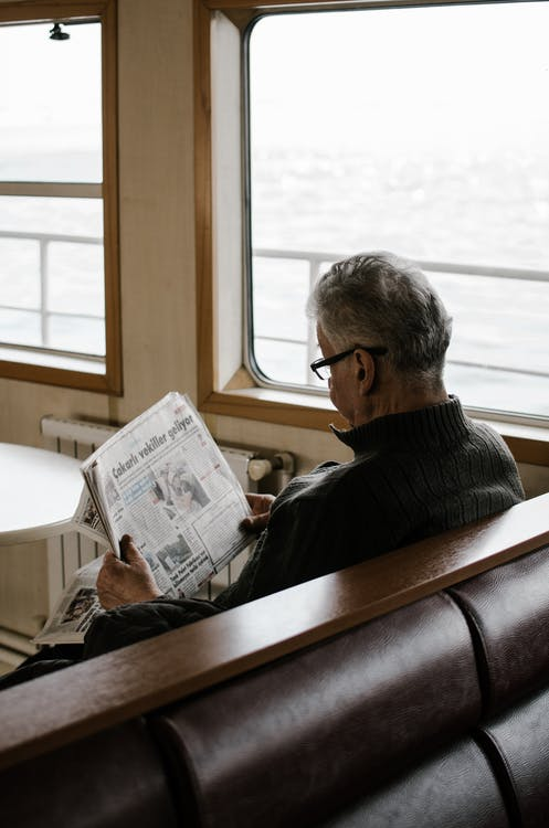 Man Sitting on Bench While Reading Newspaper