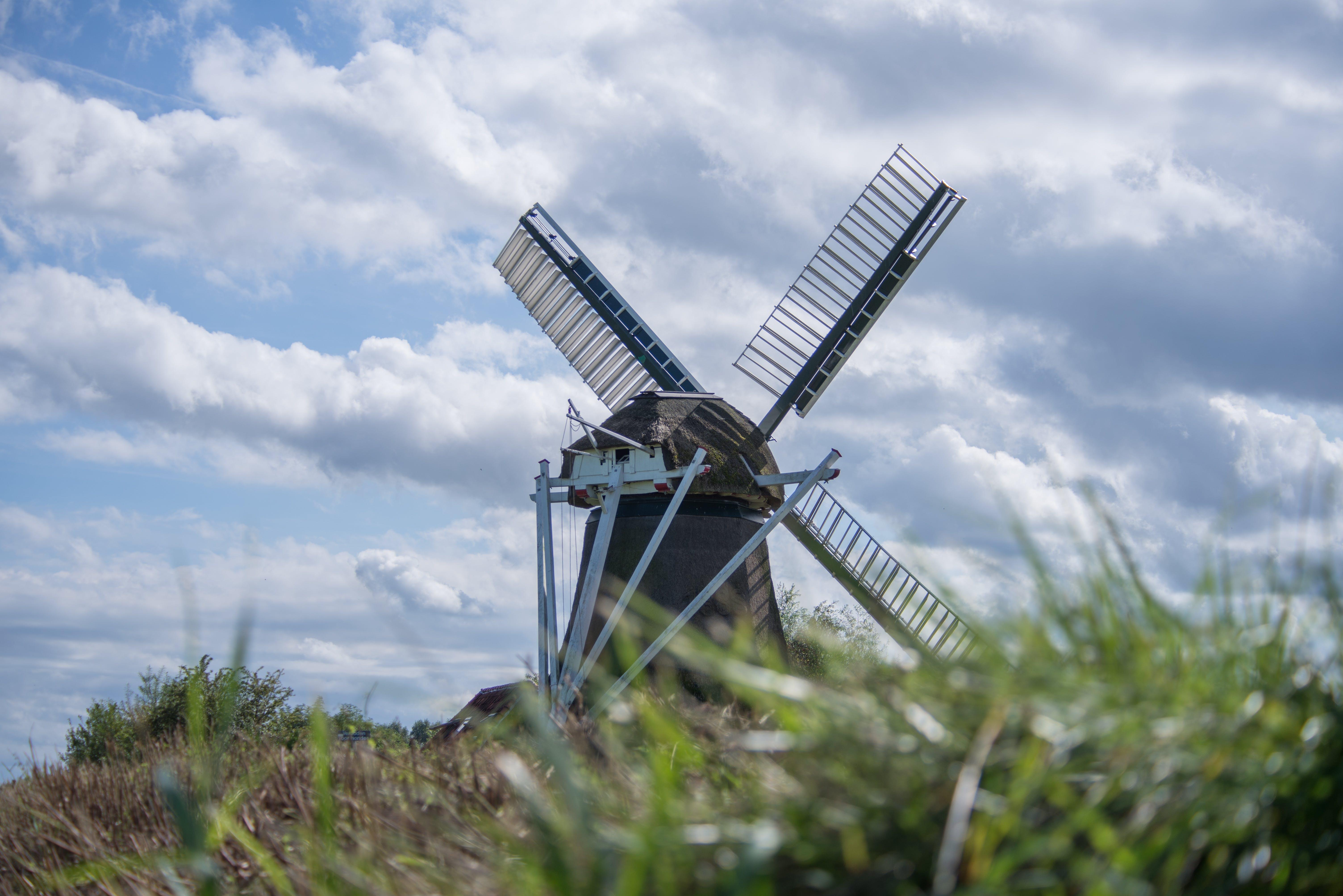 Green Grass Near Gray Windmill
