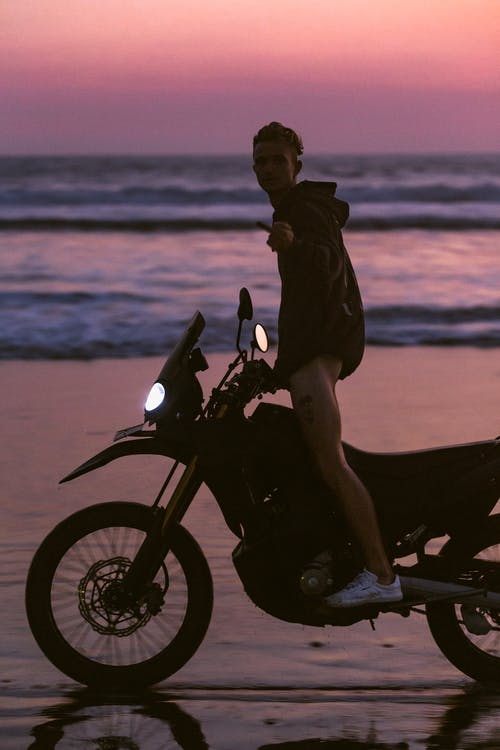Man in Black Jacket Riding Motorcycle on Seashore during Sunset