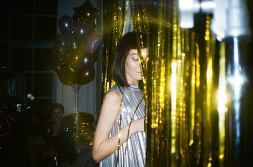 Woman Hiding Behind Gold Foil Curtain
