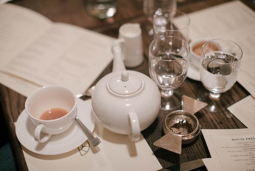 Almost Empty Teacup by Teapot and Drinking Glass Cups at Table Top