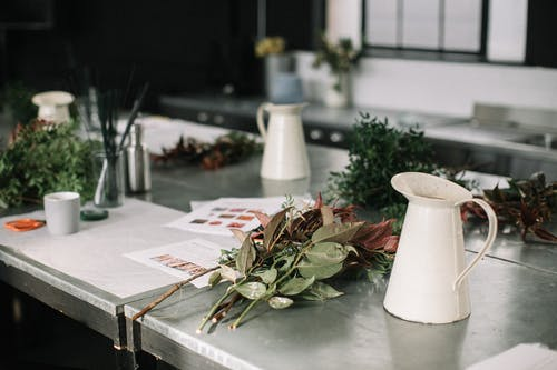 White Metal Pitchers on Table Top by Flowers