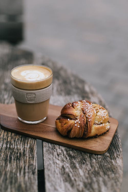 Bread and Clear Glass Cup on Wooden Board