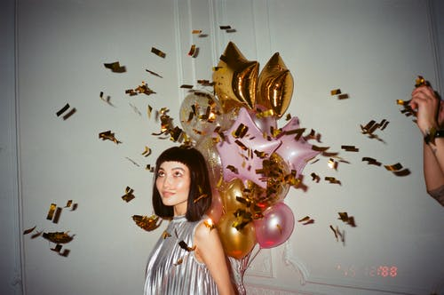Woman in Silver-blouse Holding Balloons