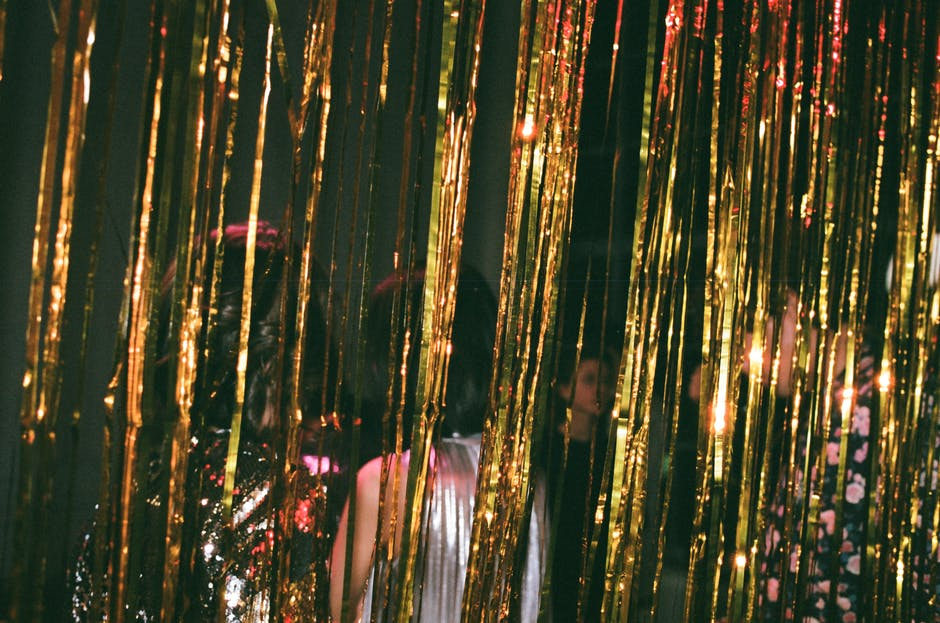 People standing behind glistening strips of gold curtain