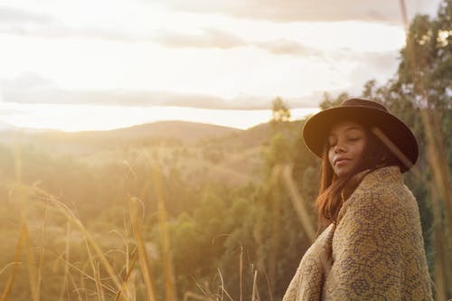 Woman With A Hat And Blanket With Background View Of Nature