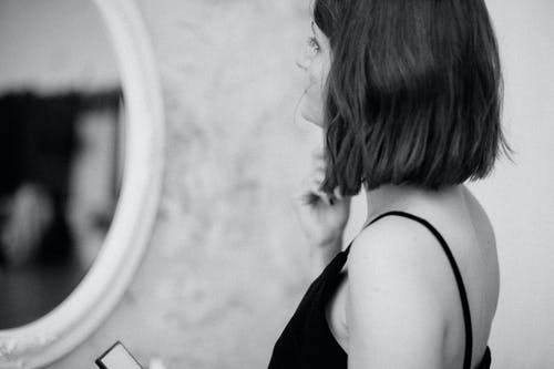 Grayscale Photo of Woman Standing in Front of Mirror