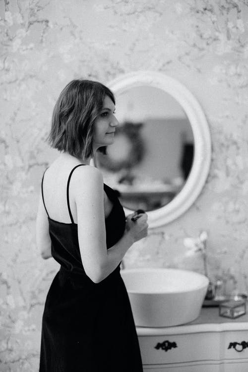 Grayscale Photography of Woman Standing in Front of a Vanity Sink