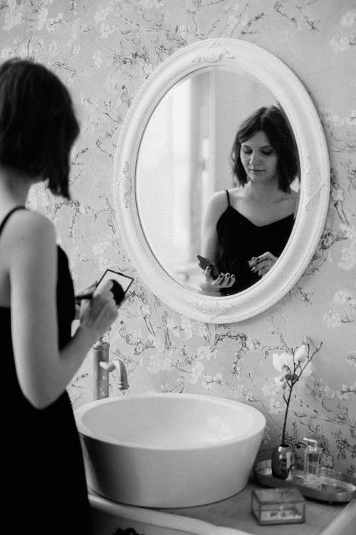 Grayscale Photo of Woman in Front of Mirror