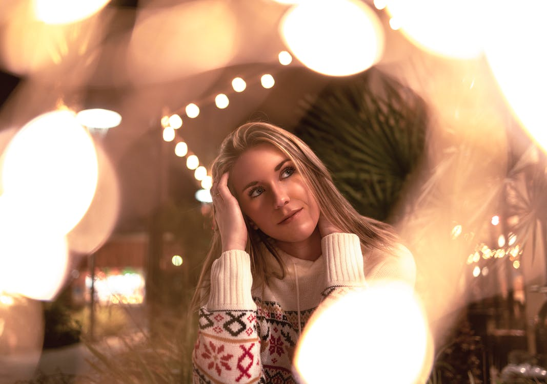Woman in Sweater by String Lights