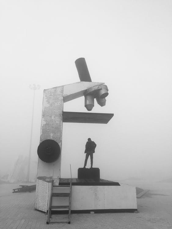 Grayscale Photography of Person Standing on Big Microscope