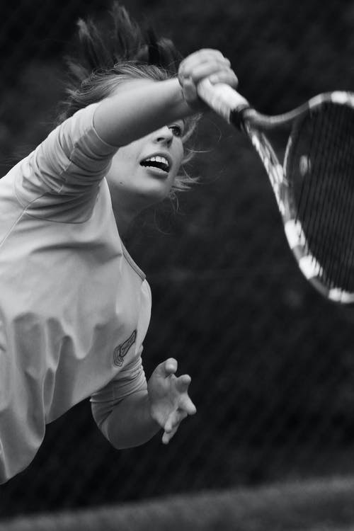 Grayscale Photo of Woman Playing Tennis