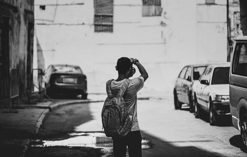 Grayscale Photography of Man Standing Outdoors