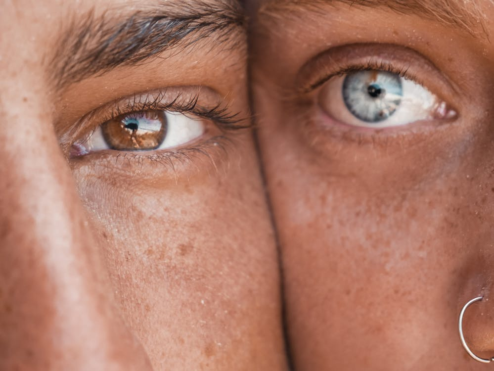 Portrait Photography of Two Person's Brown and Blue Eyes