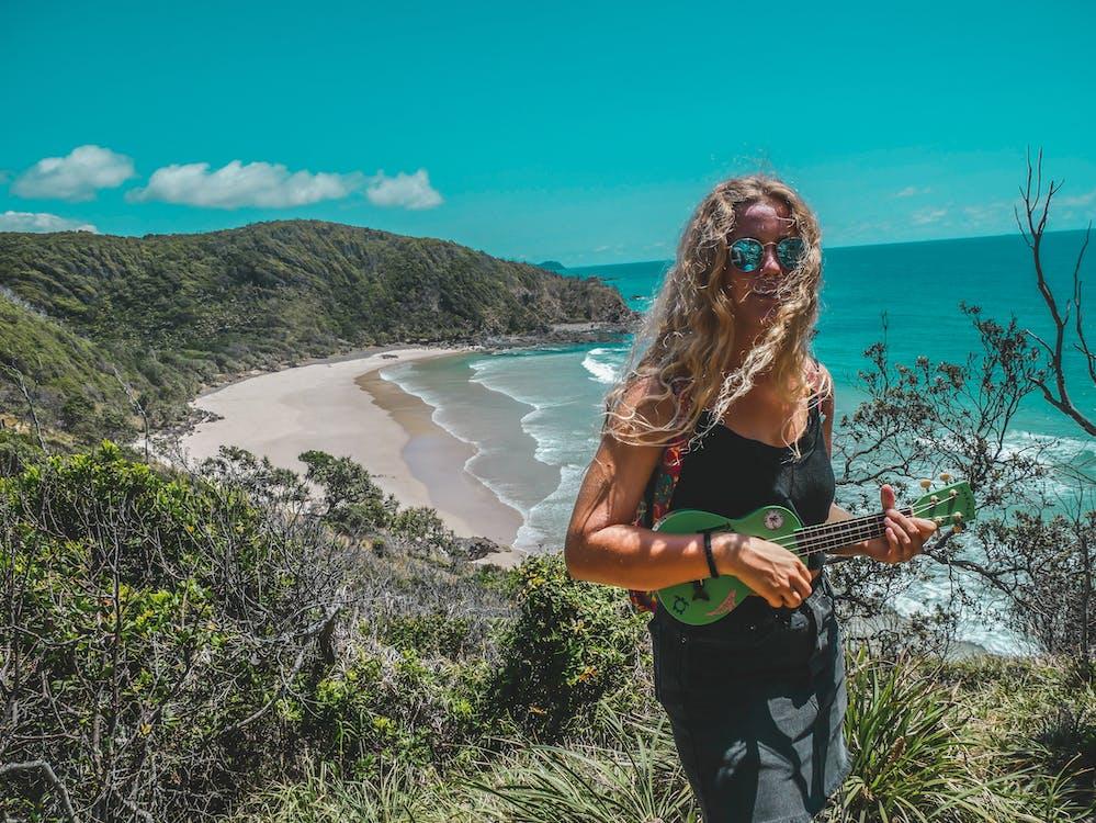 Woman Standing on Mountain While Playing Guitar Near Seashore