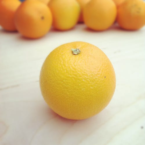 Selective Focus Photography of Orange Fruit on Beige Wooden Surface