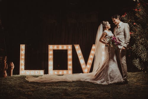 Groom and Bride Standing Beside a Love Marque Light Signage