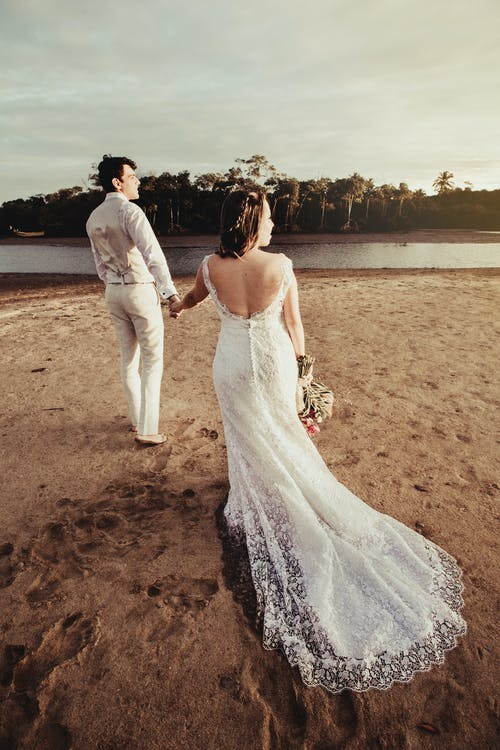 Groom and Bride Standing Near Body of Water