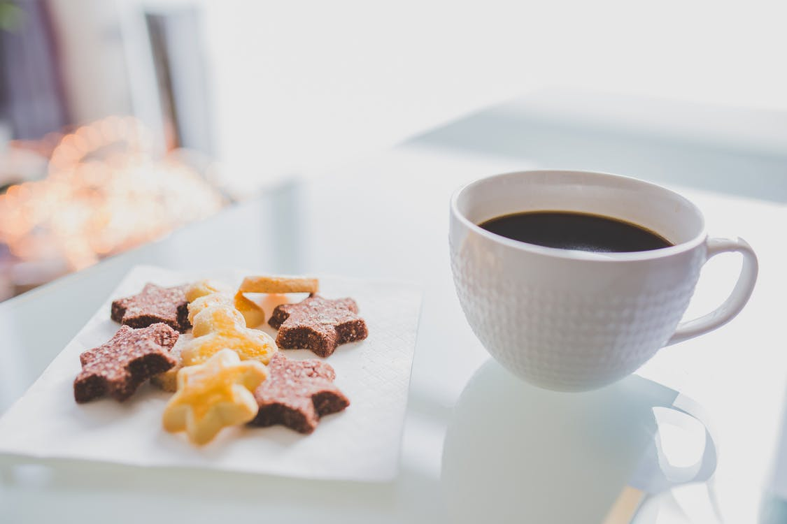 White Tea Cup Beside White Square Saucer With Star Shaped Cookies