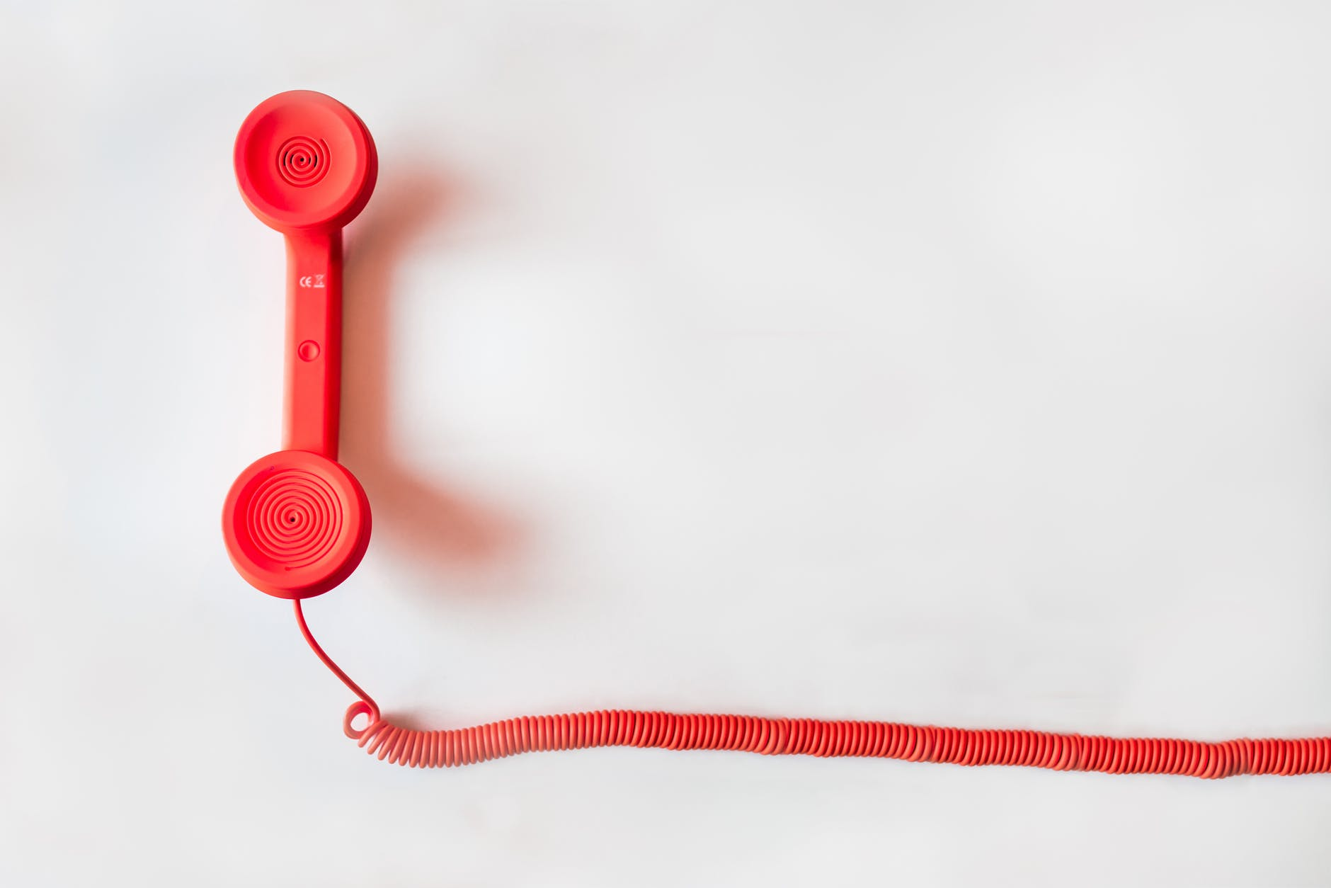 A photo of a red handheld telephone on a white background.