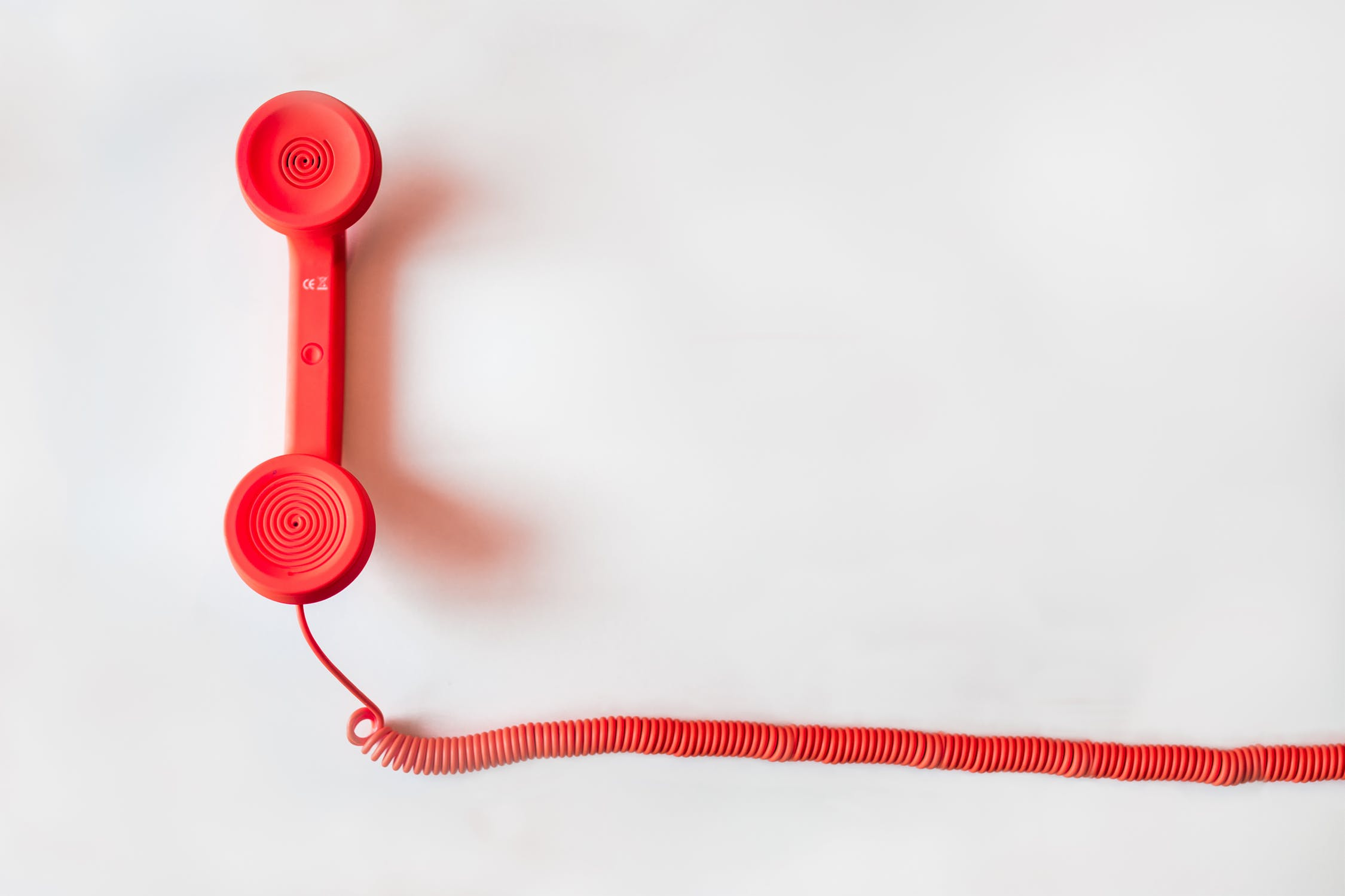 A red corded telephone sits on a white background. Photo by pexels user negative space. Photo used courtesy of Pexels.com