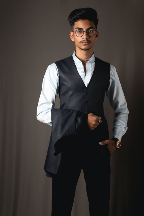 Well dressed young ethnic male looking at camera with hand in pocket