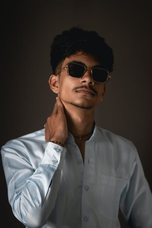 Trendy bearded young ethnic male millennial in white shirt and sunglasses standing against gray background
