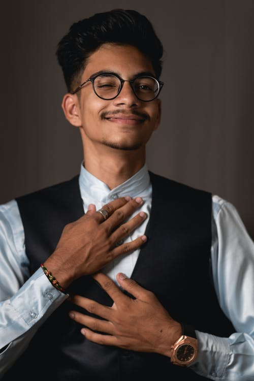 Cheerful young Indian guy in elegant suit winking against gray background