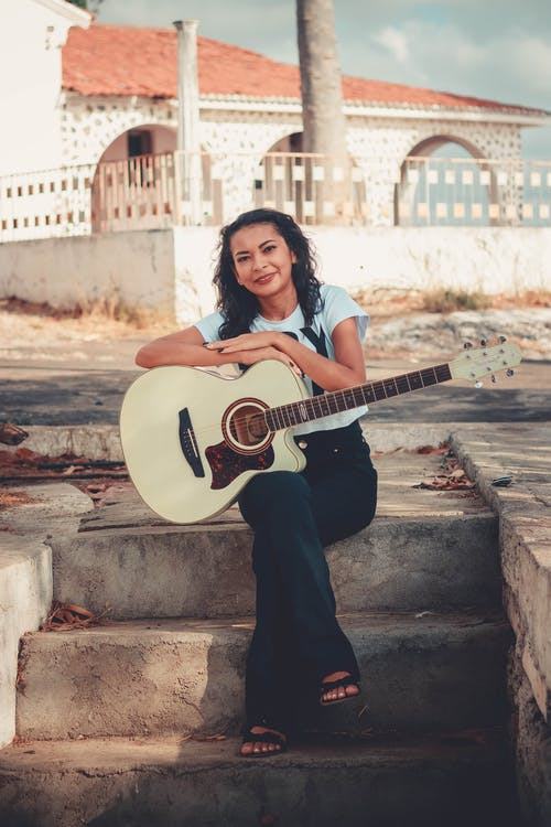 Smiling Woman Wearing White and Black Crew-neck T-shirt Holding Guitar White Sitting With Crossed Legs on Gray Concrete Stairs