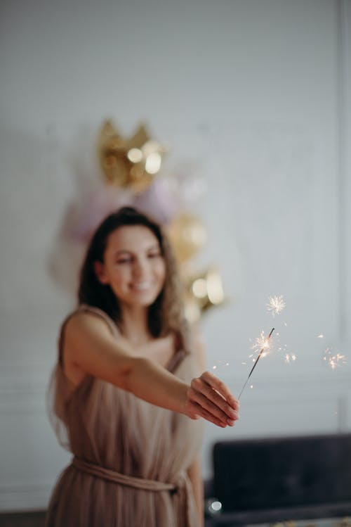 Shallow Focus Photo of Woman in Brown Sleeveless Dress Holding Sparkle