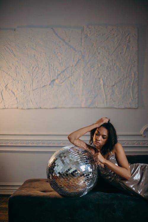 Женщина, опираясь на серебряный дискотечный шар