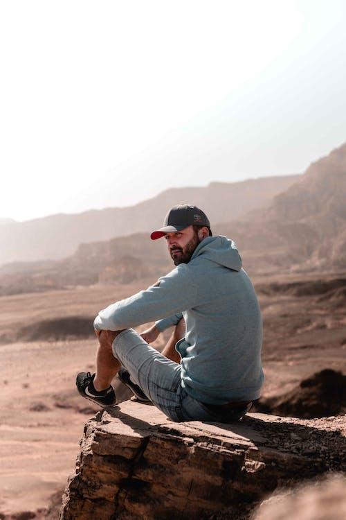 Mann Im Grauen Hoodie Und In Den Grauen Hosen, Die Auf Brown Rock Sitzen