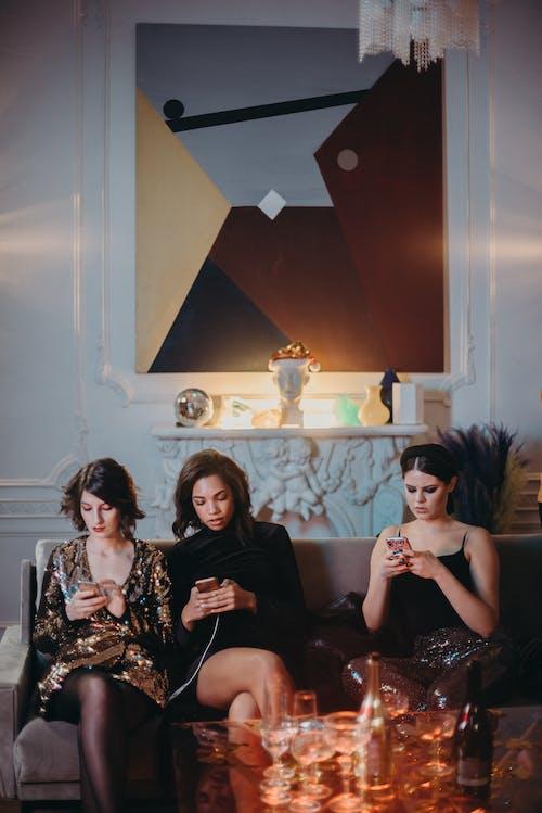 Three Women Sitting on Sofa Using Smartphone