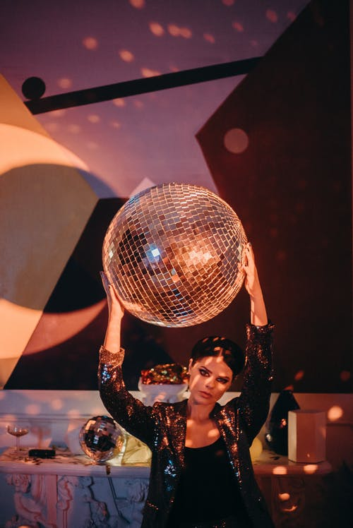 Photo of Woman Holding a Disco Ball