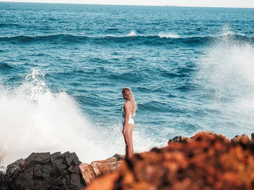 Woman in White Swimsuit Standing on Rock by the Sea