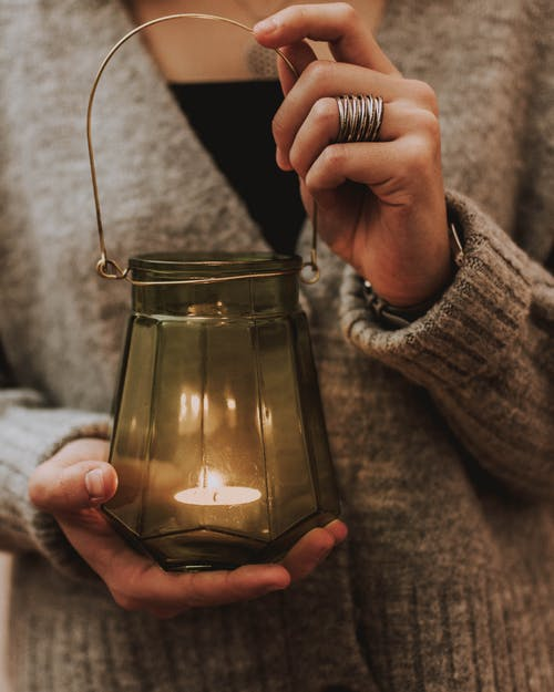 Photo of Person's Hands Holding Candle Lamp