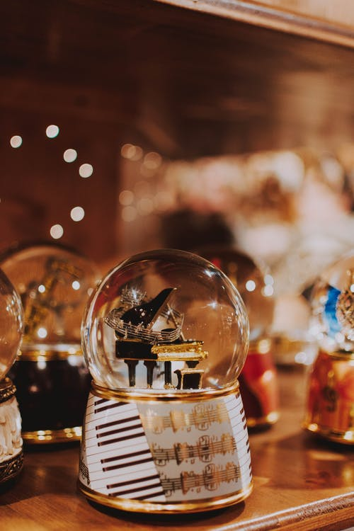 Beautiful glass ball souvenir with miniature piano inside decorated with music notes placed on wooden shelf in traditional market