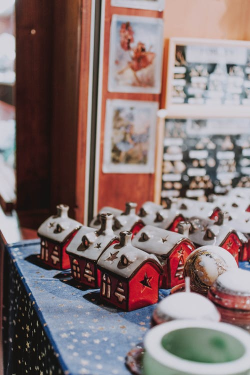 From above of beautiful small red decorative houses placed on table in row in souvenir shop during Christmas holidays